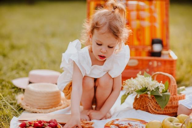 Vrij jong meisje in witte zomerblouse met picknick in het park. zomertijd.
