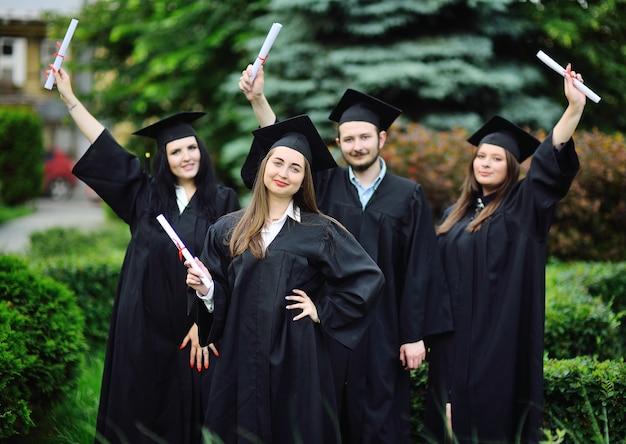 Vrij jong meisje is een afgestudeerde student in een zwart gewaad glimlachend met een diploma in haar handen tegen de achtergrond van een groep afgestudeerden.