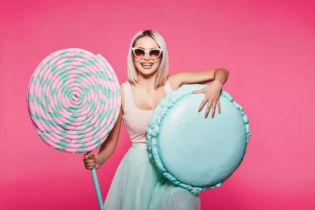 Vrij jong meisje met blond haar dat top en rok draagt die zich met enorme zoete lollypop bevindt