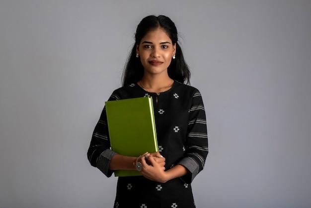 Vrij jong meisje met boek en poseren op een grijze achtergrond