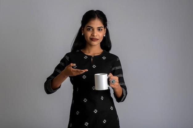 Vrij jong meisje met een kopje thee of koffie die zich voordeed op een grijze achtergrond