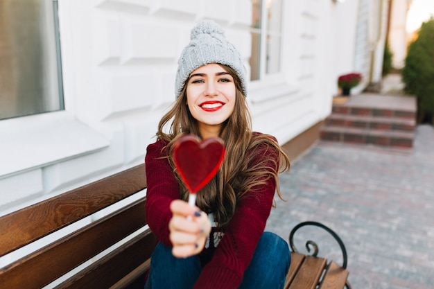 Vrij jong meisje met lang haar, zittend op een bankje op straat. ze rekte het hart van karamel uit en glimlachte.