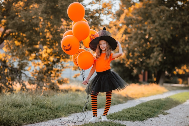 Vrij jong meisje met oranje halloween-ballonnen en shirt, zwarte rok, hoed en heksensokken die op straat poseren. halloween-concept. ruimte kopiëren.