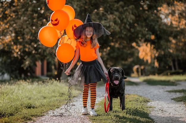 Vrij jong meisje met oranje halloween-ballonnen en shirt, zwarte rok, hoed en heksensokken die op straat poseren met zwarte labrador retriever. halloween-concept. ruimte kopiëren.