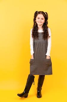 Vrij jong meisje poseren met gele achtergrond