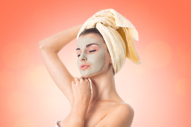 Vrij jong meisje zorgt voor haar huid met reinigingsmasker op gezicht en handdoek op hoofd geïsoleerd op een witte achtergrond. gezondheidszorgconcept. lichaamsverzorgingsconcept. jonge vrouw met een gezonde huid.