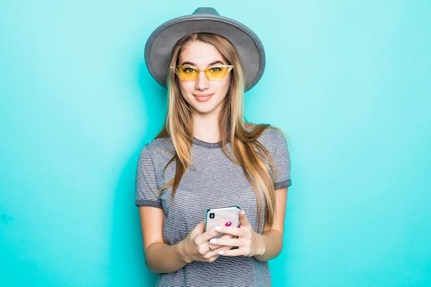 Vrij jong model in maniert-shirt, hoed en transparante bril met telefoon in haar handen die op groene achtergrond wordt geïsoleerd