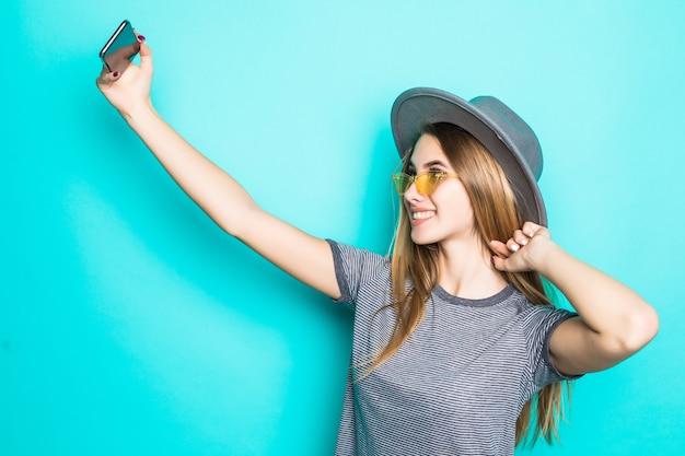 Vrij jong model in modet-shirt, hoed en transparante bril met telefoon in haar handen maakt selfie geïsoleerd op groene achtergrond