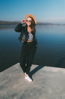 Vrij jong model meisje vrouw poseren in herfstdag aan de waterkant van het meer gekleed in vrijetijdskleding
