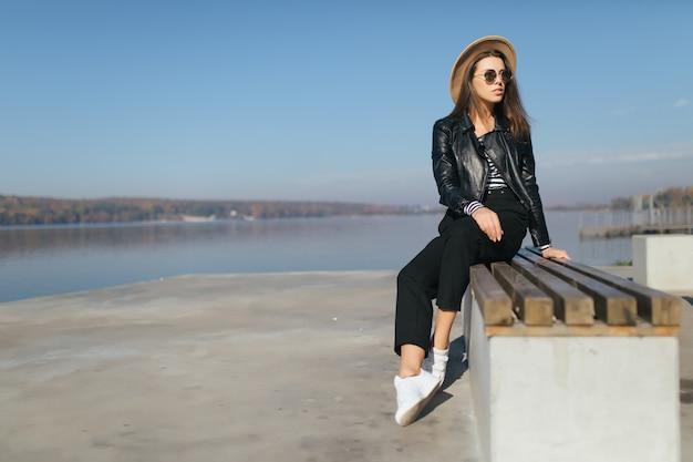 Vrij jong model meisje vrouw poseren zittend op de bank in de herfstdag aan de waterkant van het meer