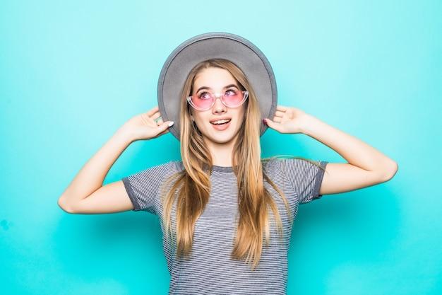 Vrij jong model met gouden haar in maniert-shirt, hoed en transparante bril die op groene achtergrond wordt geïsoleerd