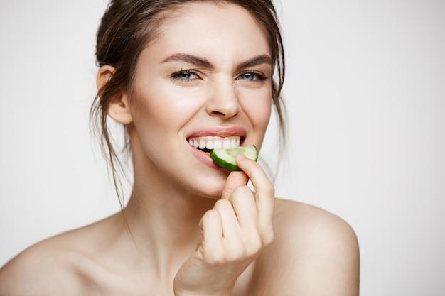 Vrij jong natuurlijk meisje dat met perfecte schone huid camera bekijkt die komkommerplak eet over witte achtergrond. gezichtsbehandeling.