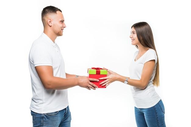 Vrij jong paar met rode giftboxverrassing die op wit wordt geïsoleerd