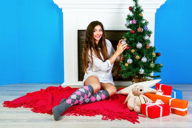 Vrij jong sensueel meisje met natuurlijke make-up en verbazingwekkende lange haren versieren kerstboom thuis. gezellige leuke vakantiesfeer.