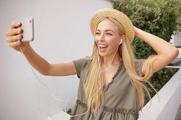 Vrij jong wijfje met lang blond haar dat haar strohoed vasthoudt en zelfportret maakt op de mobiele camera, breed glimlachend en er gelukkig uitziet