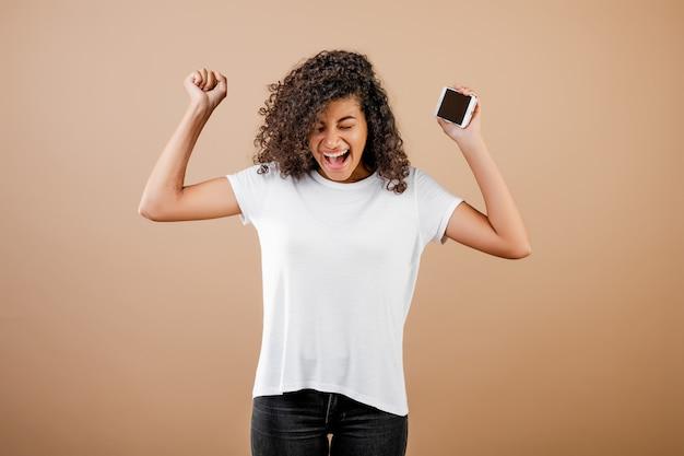 Vrij jong zwart meisje met telefoon in hand geïsoleerd over bruin