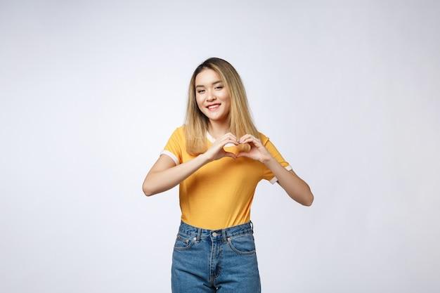 Vrij jonge aziatische vrouw die een hartgebaar met haar vingers maakt