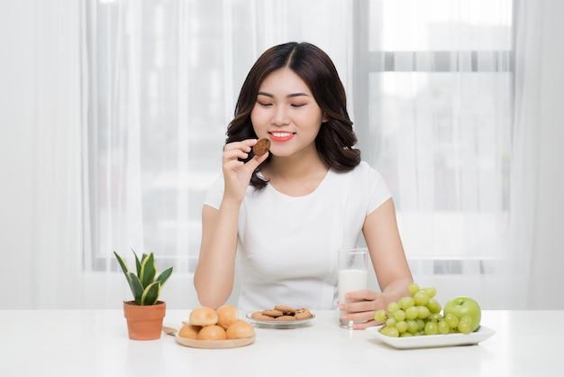 Vrij jonge aziatische vrouw die smakelijk koekje thuis eet.