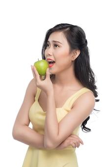 Vrij jonge aziatische vrouw die verse appel houdt die op witte achtergrond wordt geïsoleerd.