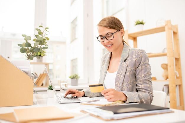 Vrij jonge beambte die persoonlijke gegevens op creditcard bekijkt tijdens het online bestellen per werkplek