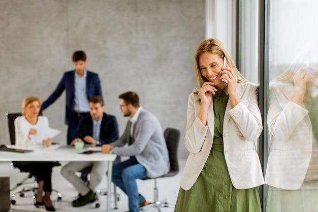 Vrij jonge bedrijfsvrouw die zich in het bureau bevindt en mobiele telefoon voor haar team gebruikt