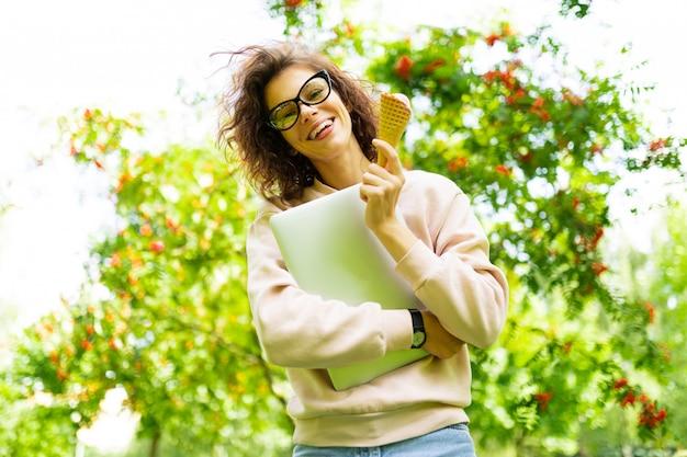 Vrij jonge blanke vrouw gaan voor een wandeling in het park met koffie en laptop