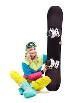 Vrij jonge blondevrouw in de kleurrijke zitting van de sneeuwkostuum met de benen over elkaar