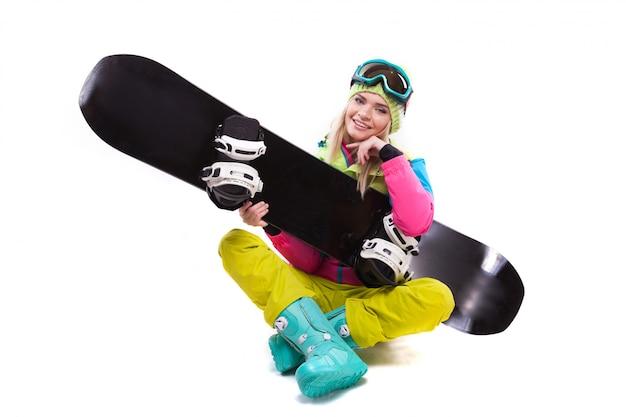 Vrij jonge blondevrouw in de kleurrijke zitting van het sneeuwkostuum met de benen over elkaar
