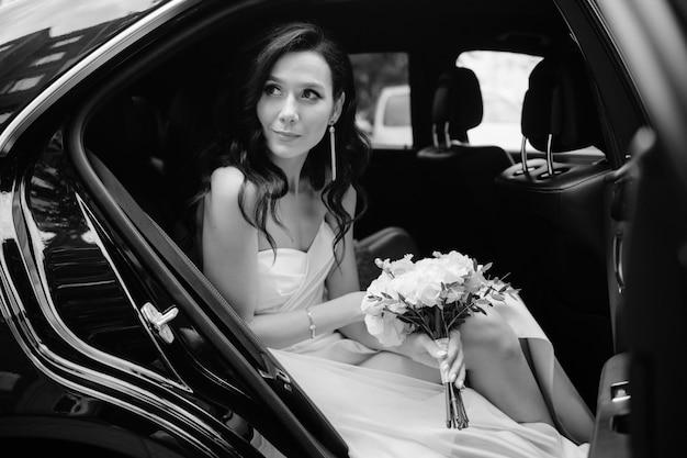 Vrij jonge bruid die uit auto kijkt.