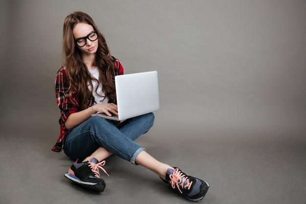 Vrij jonge dame die door laptop computer babbelt. opzij kijken.