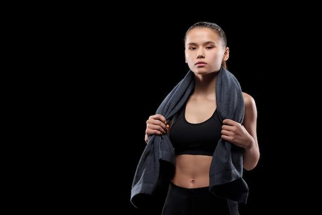 Vrij jonge geschikte sportvrouw die grijze zachte handdoek op haar hals houdt terwijl hij in isolatie staat