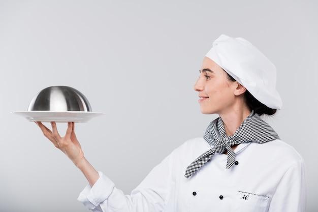 Vrij jonge glimlachende chef-kok in witte uniforme cloche met voedsel te houden en het voor camera afzonderlijk te bekijken