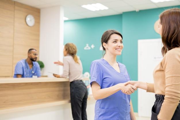 Vrij jonge glimlachende clinicus schudden hand van vrouwelijke patiënt op achtergrond van meisje raadplegen door receptie in klinieken