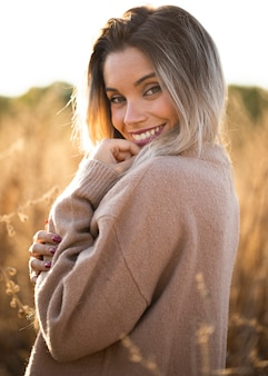 Vrij jonge glimlachende vrouw die in openlucht stellen bij