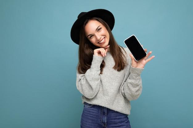 Vrij jonge glimlachende vrouw die zwarte hoed en de grijze telefoon van de sweaterholding draagt