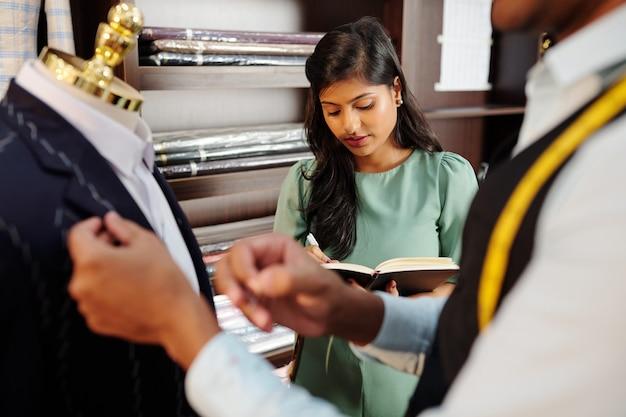 Vrij jonge indiase naaister vult document bij kleermaker metingen van jas