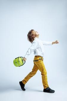 Vrij jonge jongen in vrijetijdskleding op witte muur. kaukasische mannelijke kleuter met heldere gezichtsemoties die lunchzak houden. jeugd, expressie, plezier maken. dromerig gaan en springen.
