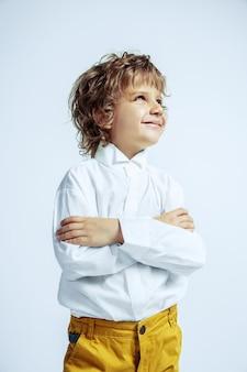 Vrij jonge jongen in vrijetijdskleding op witte muur. modieus poseren. kaukasische mannelijke kleuter met heldere gezichtsemoties. jeugd, expressie, plezier maken. poseren gekruiste handen.