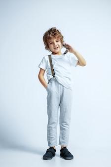 Vrij jonge jongen in vrijetijdskleding op witte muur. modieus poseren, ziet er zelfverzekerd uit. kaukasische mannelijke kleuter met heldere gezichtsemoties. jeugd, expressie, plezier maken.