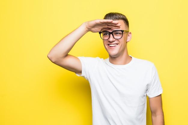 Vrij jonge jongen kijkt uit gekleed in wit t-shirt en transparante glazen geïsoleerd op geel