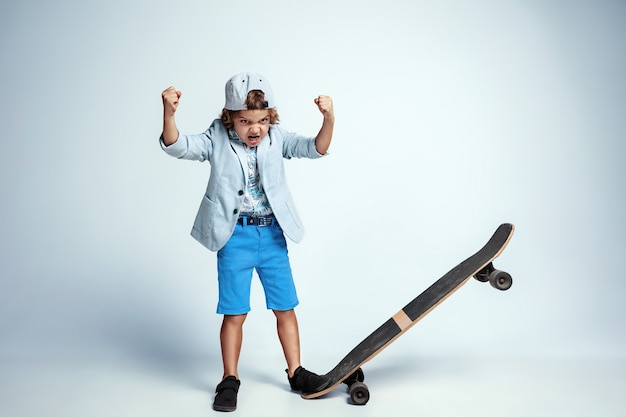 Vrij jonge jongen op skateboard in vrijetijdskleding op wit