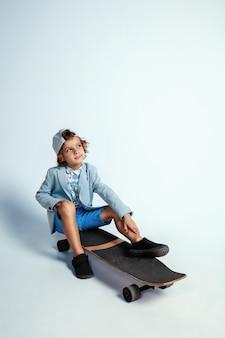 Vrij jonge jongen op skateboard in vrijetijdskleding op witte muur. rijden en ziet er gelukkig uit. kaukasische mannelijke kleuter met heldere gezichtsemoties. jeugd, expressie, plezier maken.