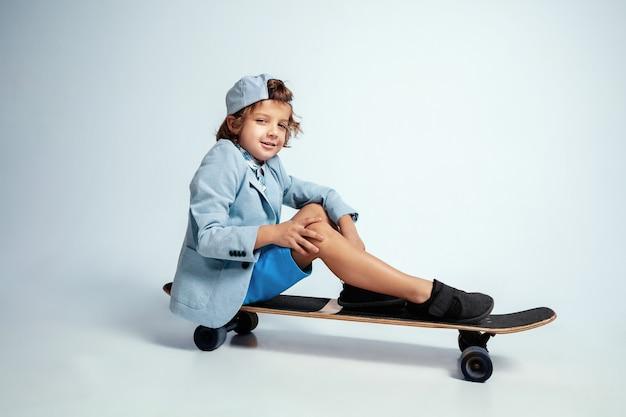 Vrij jonge jongen op skateboard in vrijetijdskleding op witte studio