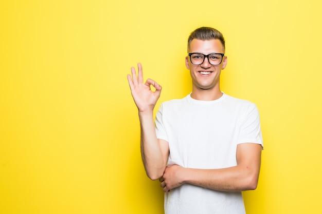 Vrij jonge jongen toont goed teken gekleed in wit t-shirt en transparante glazen geïsoleerd op geel
