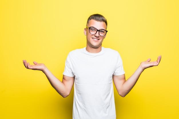 Vrij jonge jongen toont niets teken gekleed in een wit t-shirt en een transparante bril