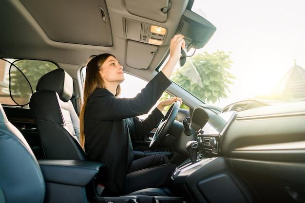 Vrij jonge kaukasische onderneemster in formele slijtage die in bestuurderszetel zit in haar auto en de centrale achteruitkijkspiegel controleert