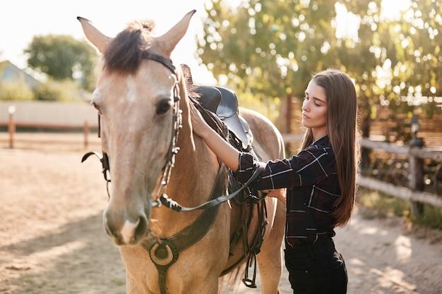 Vrij jonge kaukasische vrouw die in gecontroleerd overhemd haar bruin verzorgt