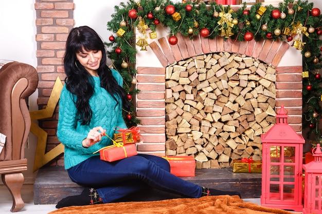 Vrij jonge kaukasische vrouwenzitting dichtbij een decoratieve open haard met kerstmisdecoratie