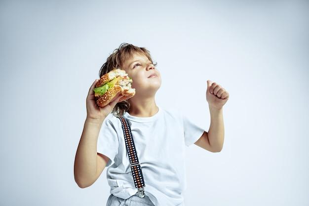Vrij jonge krullende jongen in vrijetijdskleding op witte muur. hamburger eten. kaukasische mannelijke kleuter met heldere gezichtsemoties. jeugd, expressie, plezier, fast food. dromerig kijkt op.