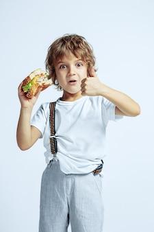 Vrij jonge krullende jongen in vrijetijdskleding op witte muur. hamburger eten. kaukasische mannelijke kleuter met heldere gezichtsemoties. jeugd, expressie, plezier, fast food. duim omhoog laten zien.